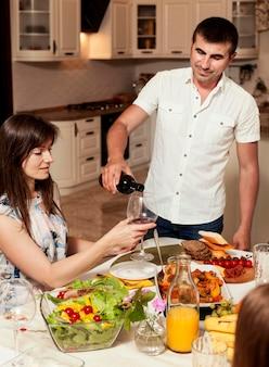 夕食の席で女性のためのワインのグラスを注ぐ男
