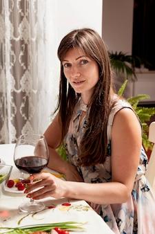 夕食のテーブルでワインを持つ女性の側面図