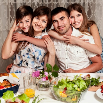 夕食のテーブルでポーズをとって幸せな家族の正面図