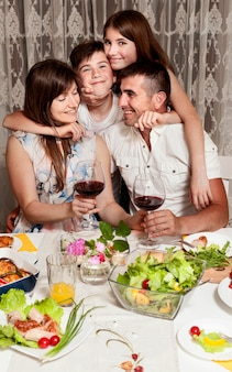 夕食のテーブルで幸せな家族の正面図