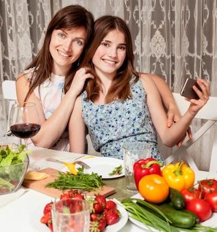 Мать и дочь позирует за обеденным столом