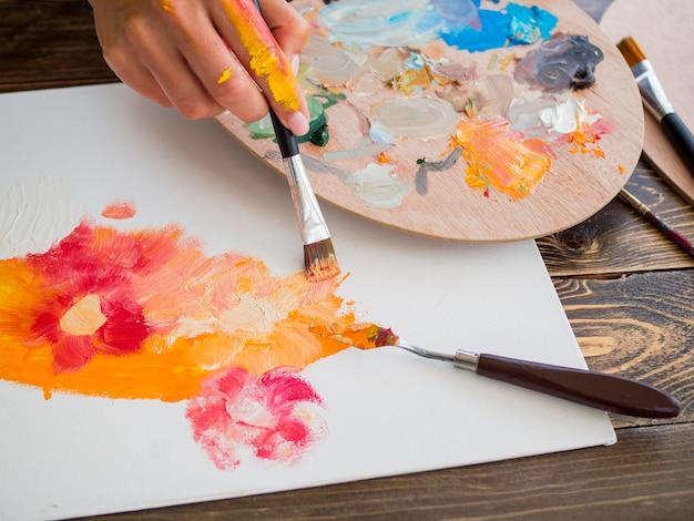 パレットとブラシでアーティストの絵画の高い角度