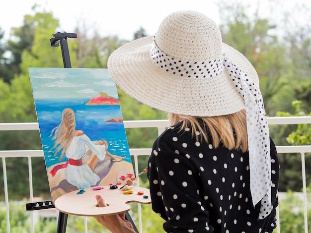 パレットでペイントする女性アーティストの側面図