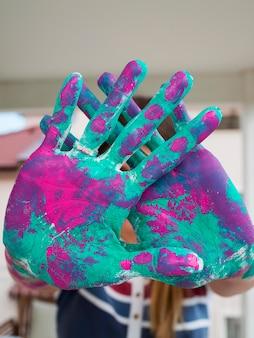塗られた手を示す人の正面図