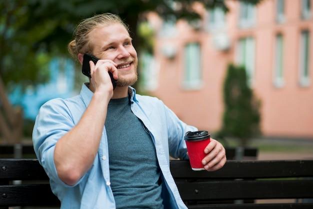 スマートフォンを屋外で取っているスマイリー男