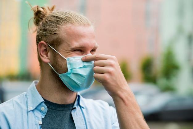 フェイスマスクを着ているスマイリー男の側面図