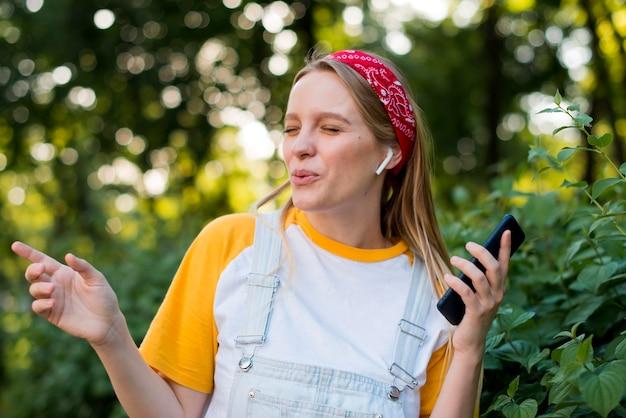 屋外で音楽を楽しむスマイリー女性