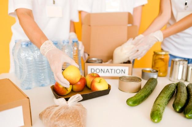 Высокий угол людей, кладущих еду в ящик для пожертвований