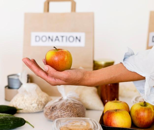 Лицо, занимающее яблоко для благотворительного пожертвования