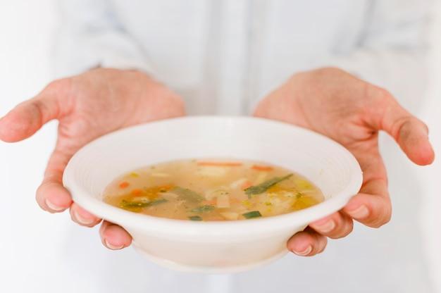 スープの器を持っている人
