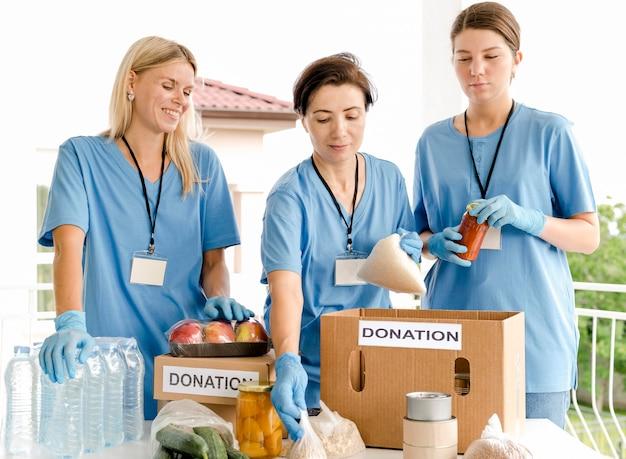 Люди кладут еду в ящики для пожертвований