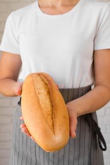 焼きたてのパンを保持している女性