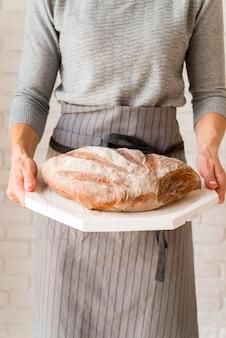 パンと木の板を保持している正面図女性