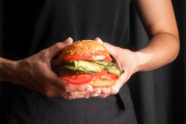 Мужчина держит вкусный гамбургер