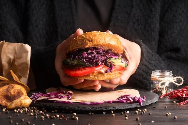 Человек готовится съесть гамбургер