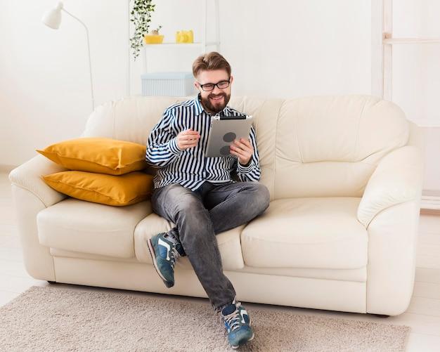 男は自宅でタブレットが付いているソファーでリラックス