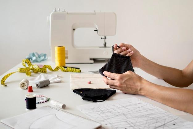 マシンで縫製フェイスマスクを保持している女性