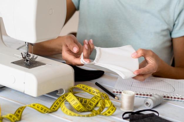 Женщина, держащая маску, она сделала с помощью швейной машины