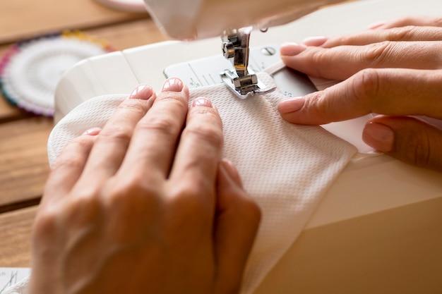 Высокий угол женщины, используя швейную машину для маски для лица