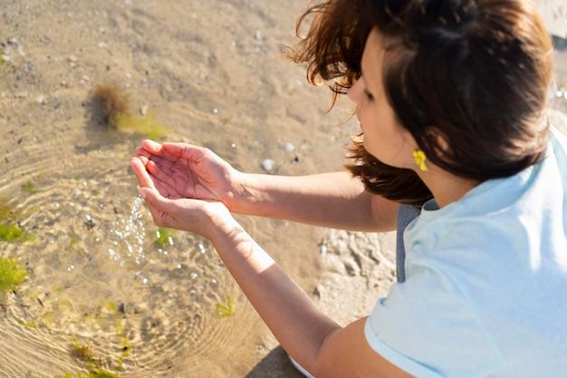 屋外の水に手を伸ばす女性の高角度