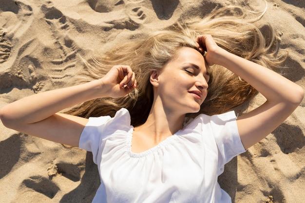ビーチの砂でポーズ女性のトップビュー