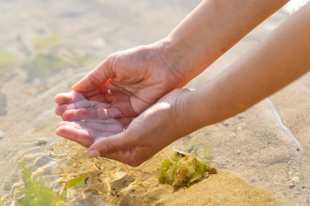 屋外できれいな水を手で保持している女性