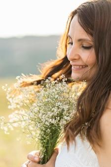Вид сбоку женщины на природе с букетом цветов