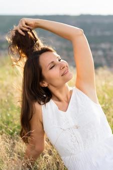 屋外の芝生でポーズをとる女性の正面図