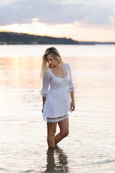夕暮れ時、海でポーズをとる女性