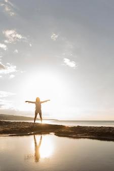太陽とビーチでポーズの女性