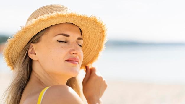 コピースペースとビーチでポーズの女性の側面図