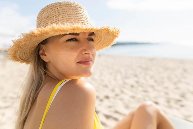 ビーチで日光浴を楽しむ女性の側面図