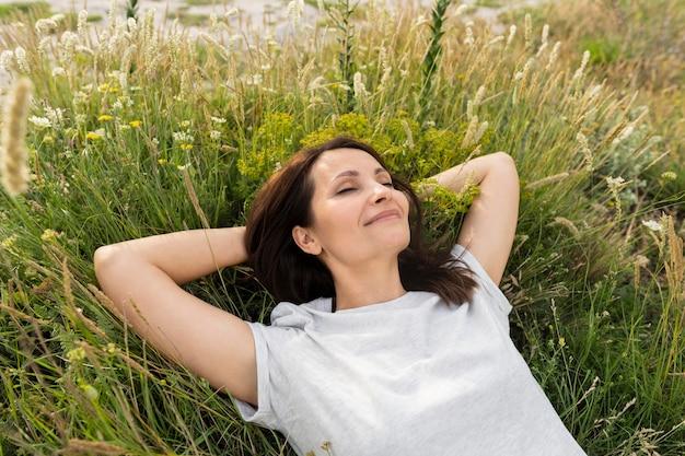 草でリラックスした女性の高角度