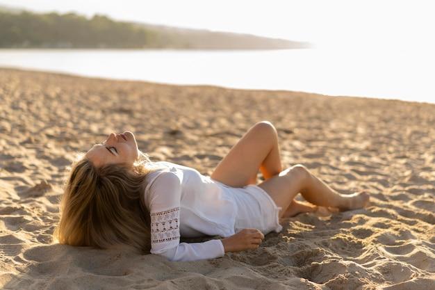浜の砂でリラックスした女性