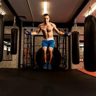 Вид спереди мужской боксер прыгает через скакалку