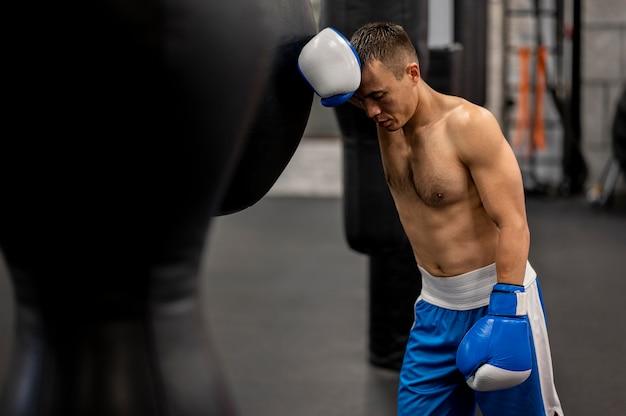 練習後休んでいる男性のボクサーの側面図