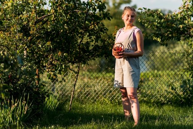 フルショットの女性がフルーツバスケットでポーズ
