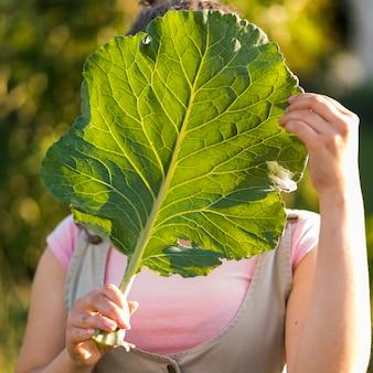 Крупным планом девушка держит лист салата