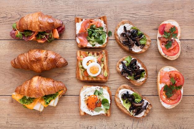 木製の背景にフラットレイアウトの新鮮なサンドイッチの配置