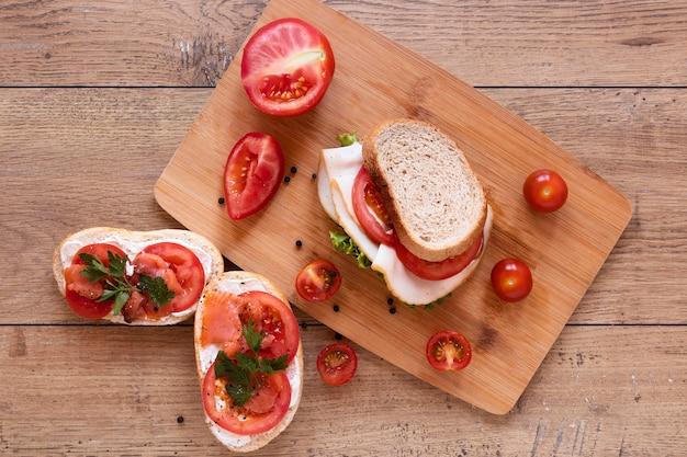 木製の背景の上から見る新鮮なサンドイッチ組成