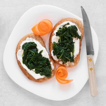 Расположение свежих бутербродов на белой тарелке