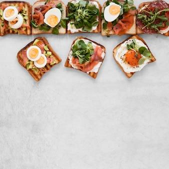 Композиция из вкусных бутербродов на белом фоне с копией пространства