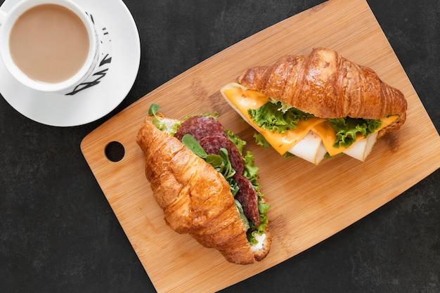 木の板においしいサンドイッチのフラットレイアウトの配置