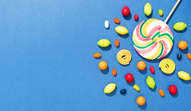 コピースペースと青色の背景にキャンディーのフラットレイアウトの配置