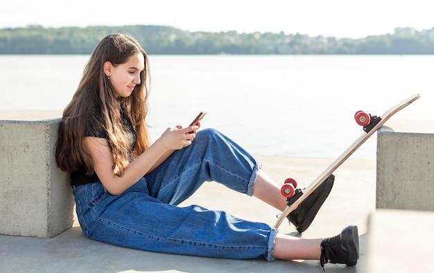 サイドビューの女の子が彼女のスケートボードの横にある彼女の電話をチェック