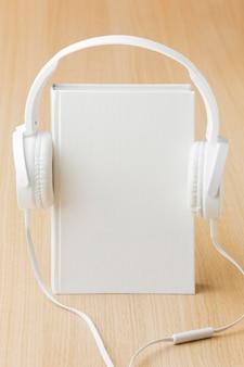 机の上の本の横にあるヘッドフォン