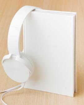 テーブルの上の本の横にあるヘッドフォン