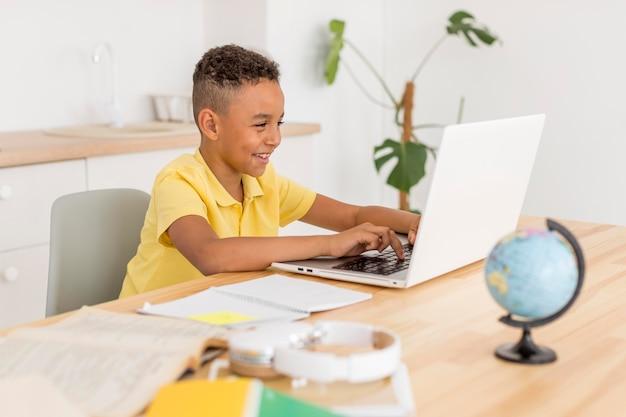 ノートパソコンを見て笑っている少年