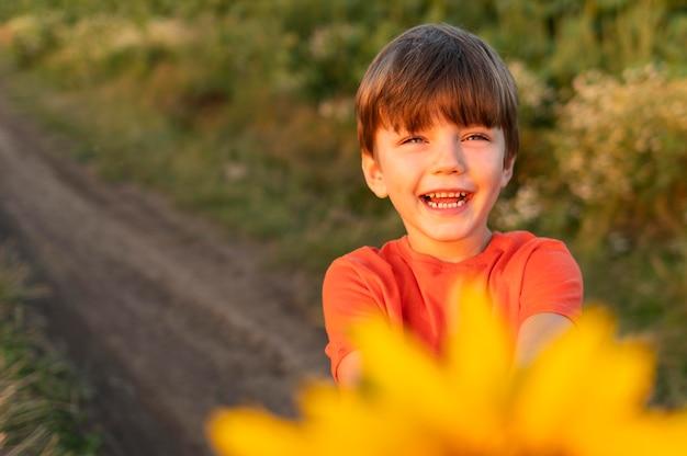 黄色い花を持つスマイリー子供