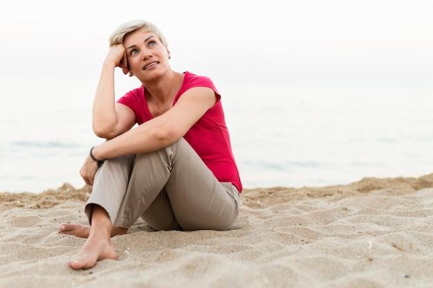 フルショットの女性がビーチでポーズ
